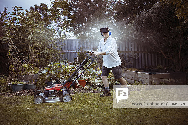 Caucasian man mowing lawn with VR goggles