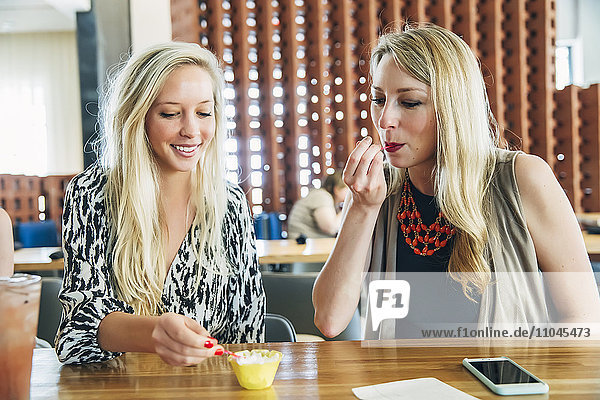 Caucasian women tasting dessert at bar