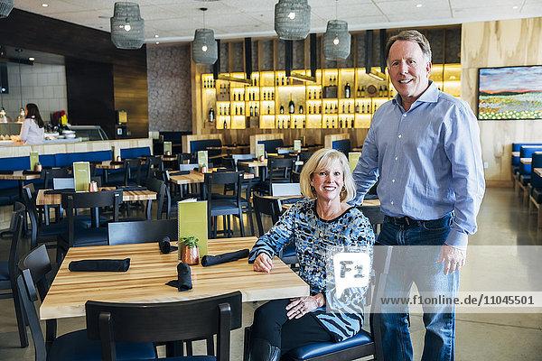 Older Caucasian couple posing in restaurant