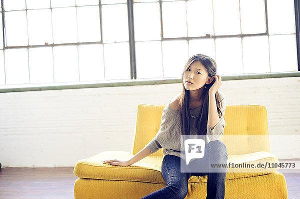 Asian woman sitting on yellow sofa