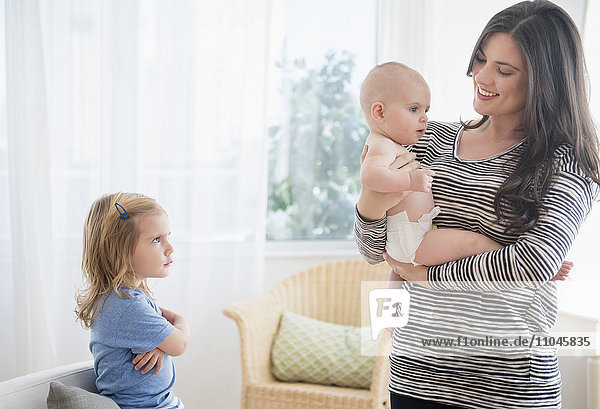 Caucasian daughter jealous of mother holding baby sister