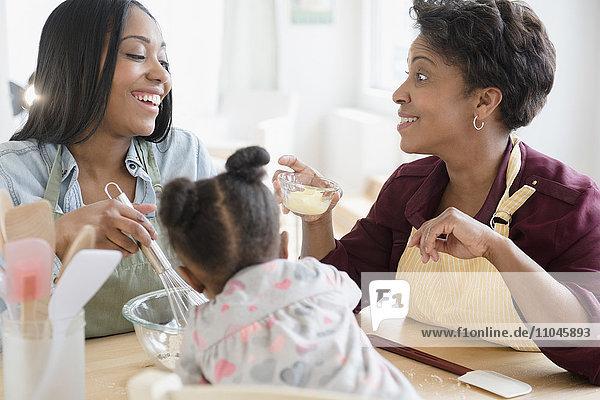 Black multi-generation family baking