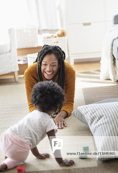 Black woman playing with baby daughter on carpet