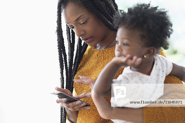 Black woman holding baby daughter using cell phone