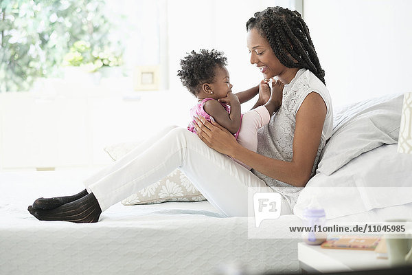 Black woman cuddling with baby daughter on bed
