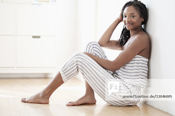 Smiling Black woman sitting on floor