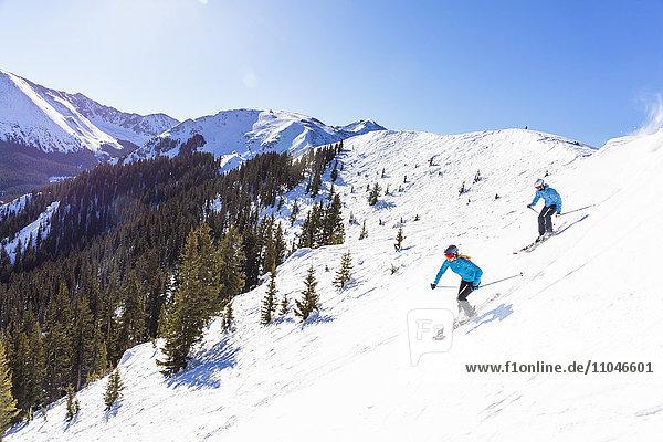 Couple skiing on snowy mountain slope