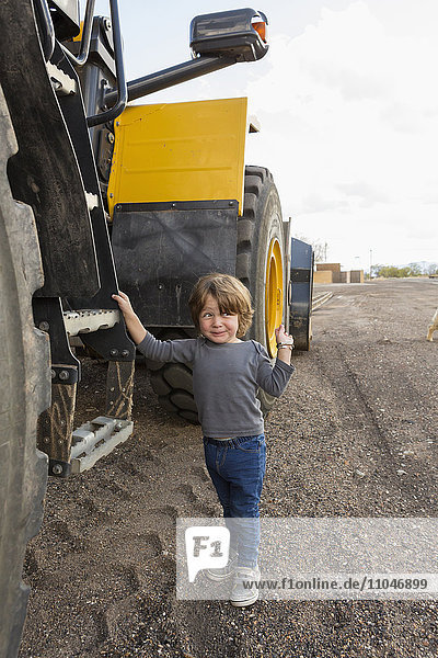 Caucasian boy holding ladder on tractor