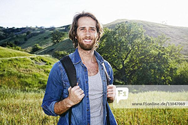 Caucasian hiker standing in grass on mountain