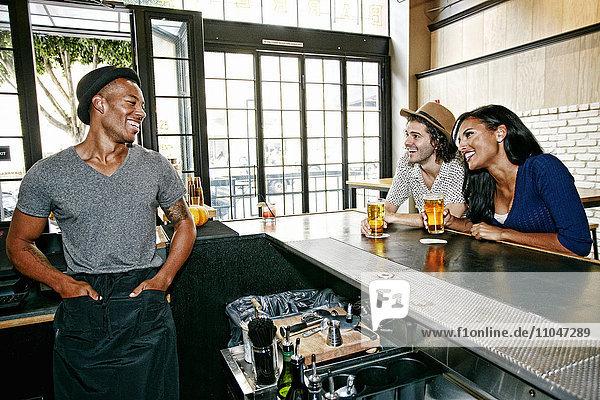 Smiling bartender and customers at bar