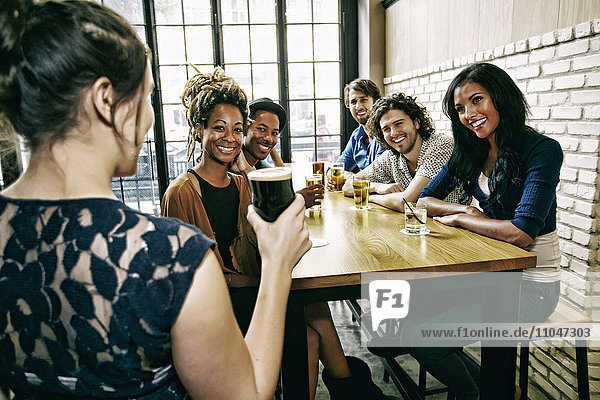Waitress serving smiling friends at table in bar