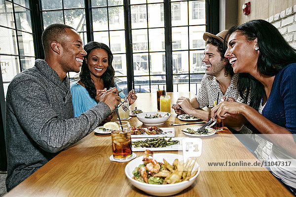 Smiling friends enjoying food and cocktails at table in bar