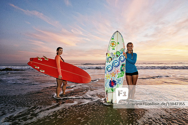Women standing in ocean waves holding surfboards at beach