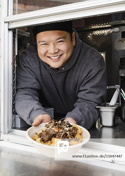 Proud Asian man showing bowl of food at food truck
