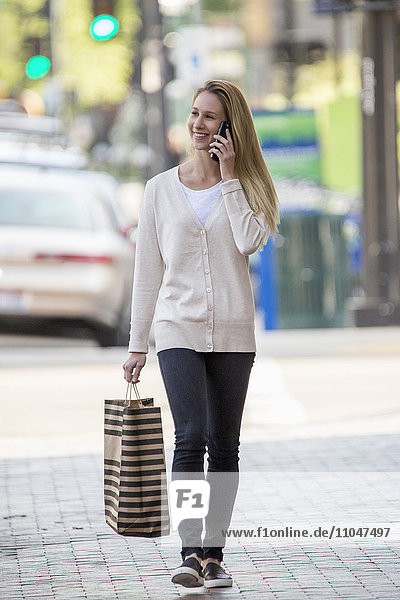 Caucasian woman carrying shopping bag using cell phone