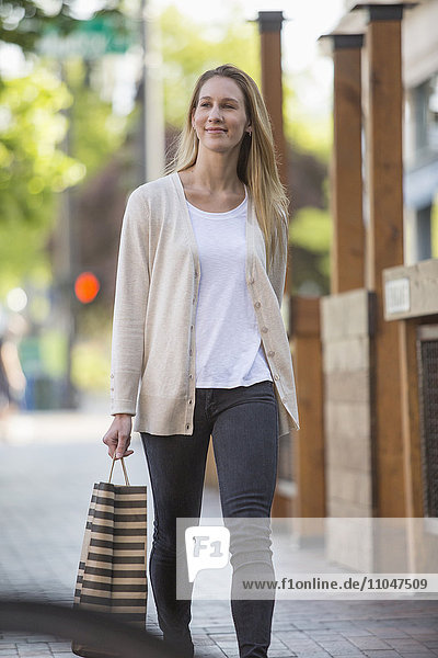 Caucasian woman carrying shopping bag in city