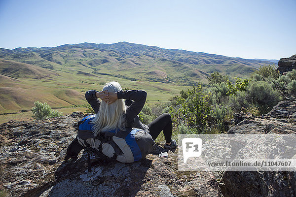 Older Caucasian woman sitting on rocks leaning on backpack