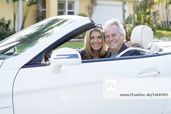 Caucasian couple smiling in convertible