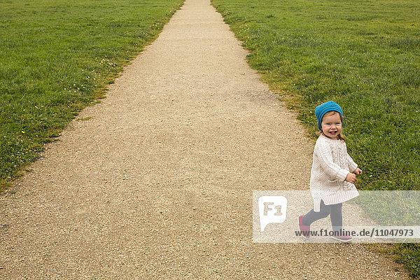 Smiling Caucasian baby girl walking on path
