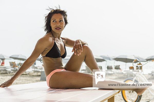African American woman sitting on deck chair on beach
