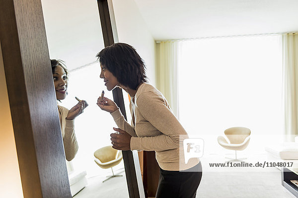 African American businesswoman applying lipstick in mirror