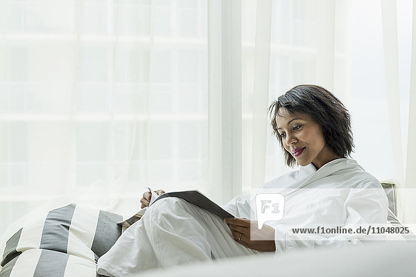 African American woman reading magazine near window