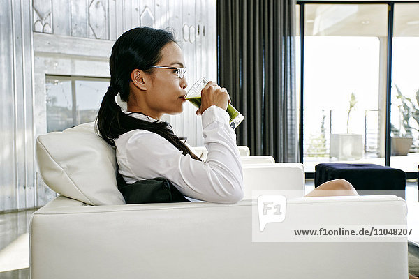 Chinese businesswoman drinking green smoothie on sofa