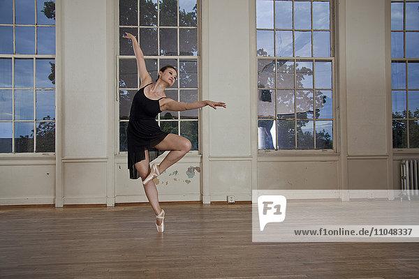Asian ballerina dancing in studio