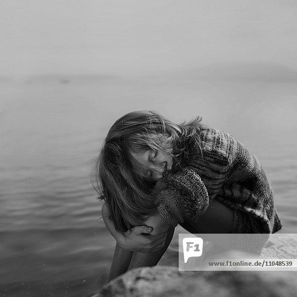 Caucasian girl sitting at remote river