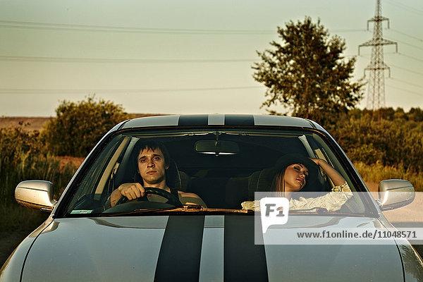 Caucasian couple driving sports car in rural landscape