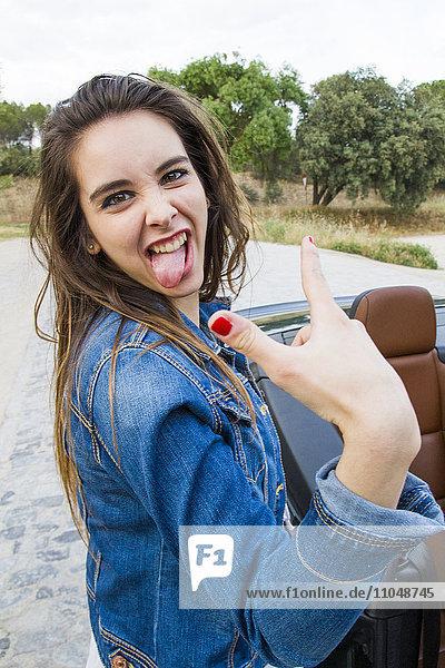Caucasian woman making a face near car