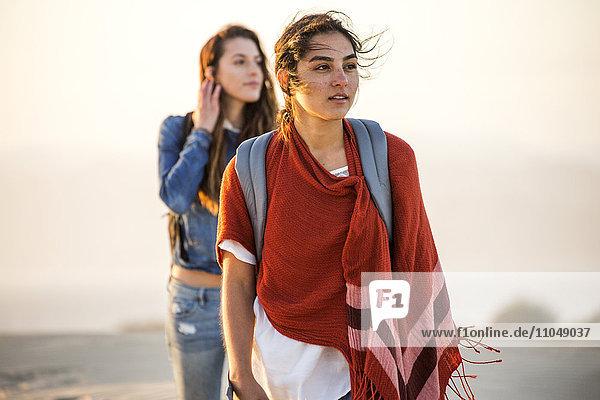 Mixed race women walking on beach