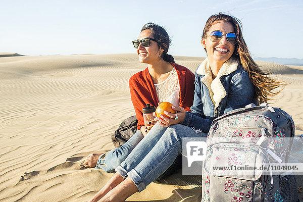 Mixed race women sitting on sand dunes