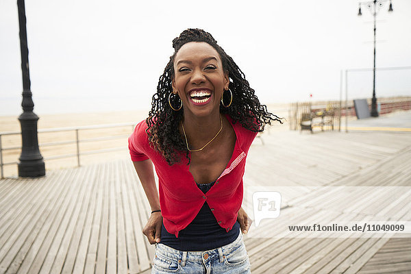 Black woman laughing on boardwalk