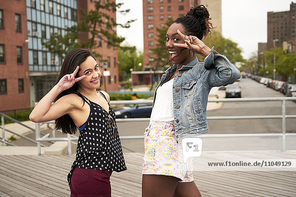 Smiling women gesturing peace on city boardwalk