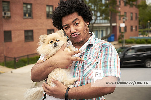 Mixed Race man gesturing peace with dog in city