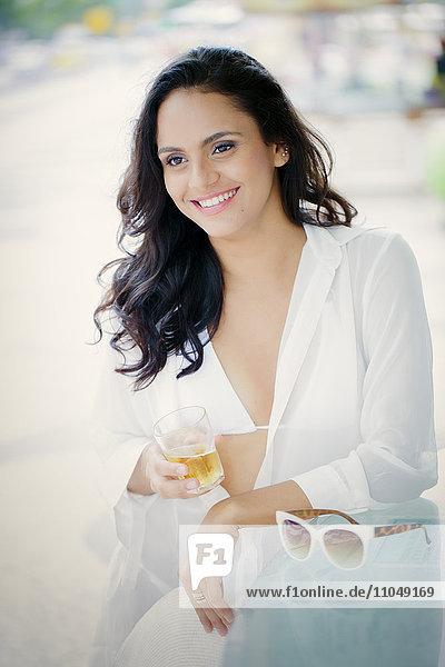 Hispanic woman drinking cocktail outdoors