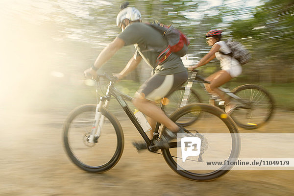 Blurred view of couple riding mountain bikes