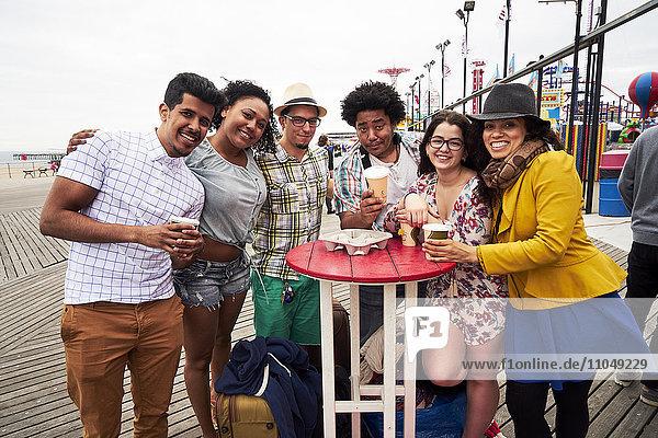 Friends drinking coffee on boardwalk at beach