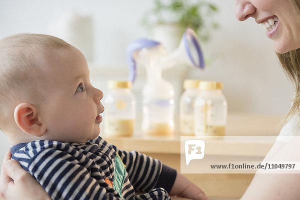 Caucasian woman holding baby son near bottles of breast milk