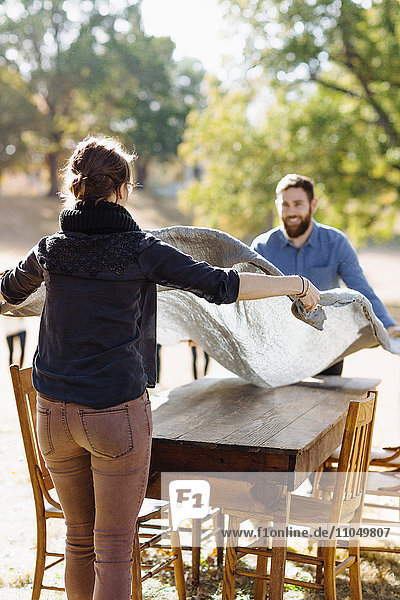 Caucasian couple spreading tablecloth on outdoor table