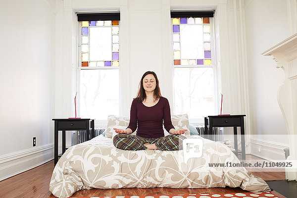 Mixed race woman meditating in bedroom