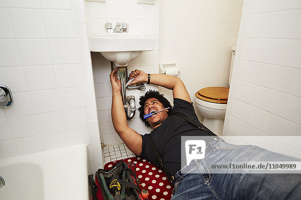 Mixed race man fixing sink plumbing
