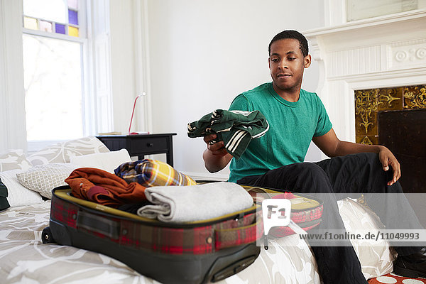 African American man packing suitcase in bedroom