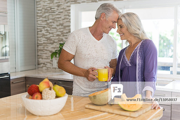 Caucasian couple touching foreheads in kitchen