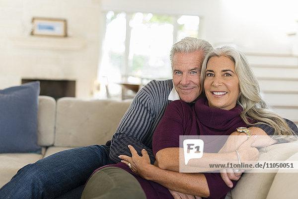 Caucasian couple hugging on sofa