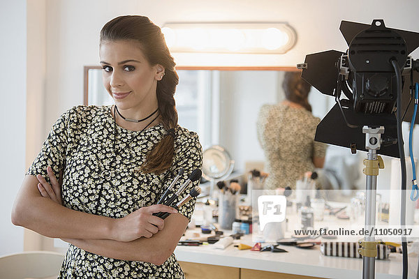 Hispanic makeup artist smiling in studio