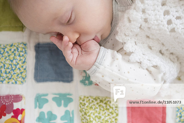 Sleeping Caucasian baby sucking thumb