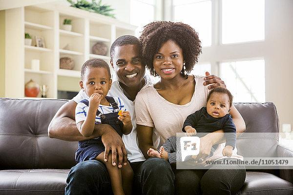 Smiling Black family posing on sofa