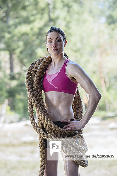 Serious Caucasian woman carrying heavy ropes